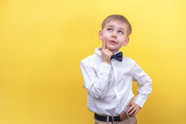 Een schattige blonde jongen in een shirt lacht en kijkt dromerig omhoog naar geel