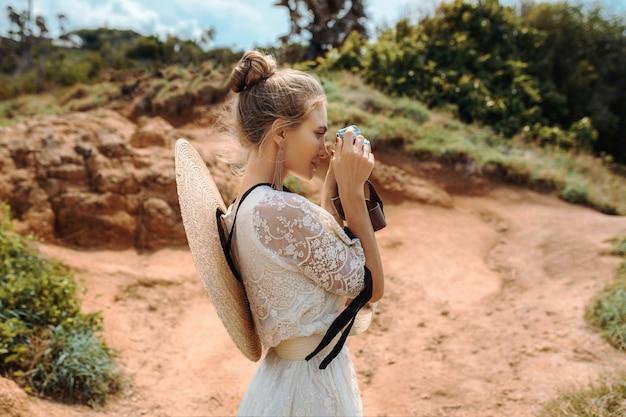 Een schattige blonde met een knot op haar hoofd in een witte luchtige jurk met massieve oorbellen in haar oren en een hoed om haar nek gebonden poseert met een fotocamera tussen kleirassen en groene struiken