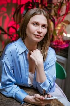 Een schattige blonde vrouw in een blauw shirt aan een tafel in een café met een telefoon in haar hand kijkt naar de camera