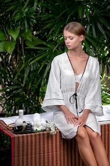 Een schattige blonde zit op een massagetafel en bestudeert items voor spa-verzorging