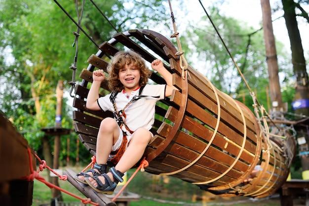 Een schattige, curly-haired jongen geniet van succes of overwinning tegen de achtergrond van een touwpark.
