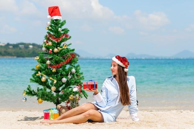 Een schattige dame in een kerstmuts met een cadeau in haar hand zit op het zand op het strand in de buurt van een aangeklede dennenboom.