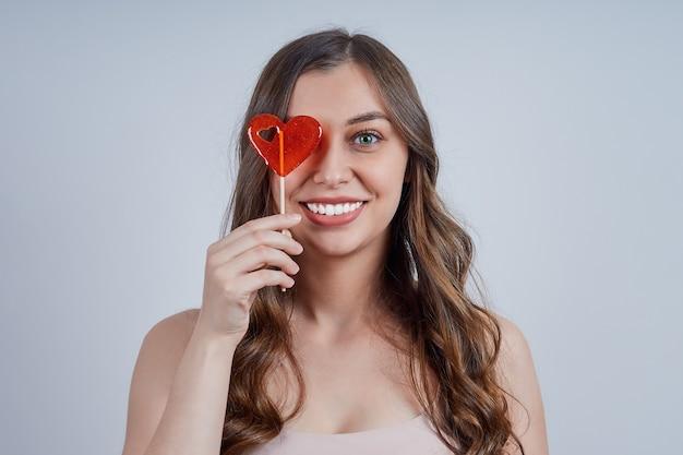 Een schattige, glimlachende blondine met een rode hartvormige lolly