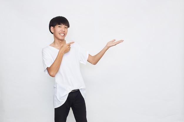 Een schattige jonge aziatische man verbaasd en lachend naar de camera terwijl hij met een hand presenteerde en met een vinger op een wit oppervlak wees