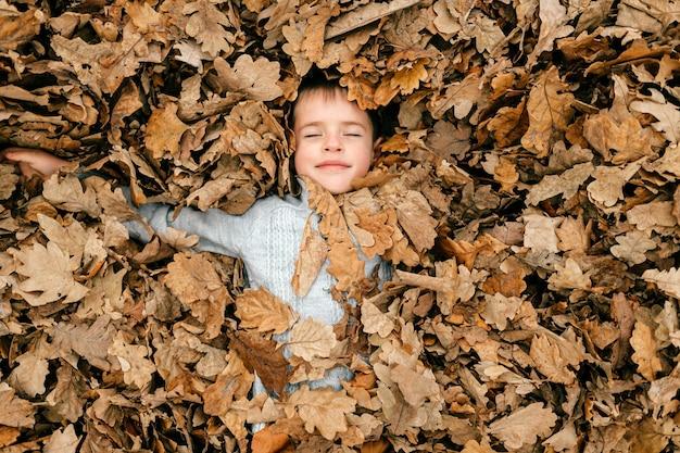 Een schattige jonge jongen die in bladeren ligt