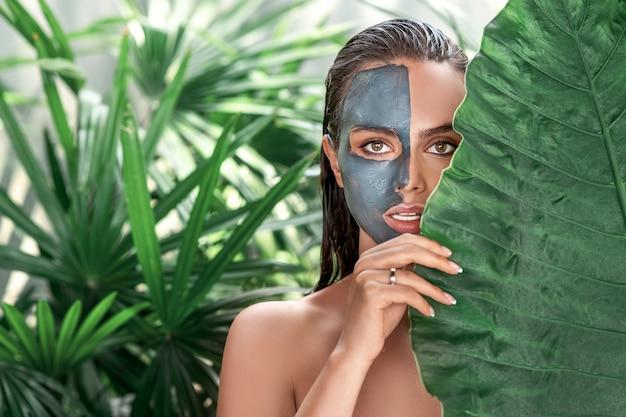 Een schattige jonge vrouw geniet van een spa, heeft een kleimasker op de helft van haar gezicht gezet, houdt een groen blad vast