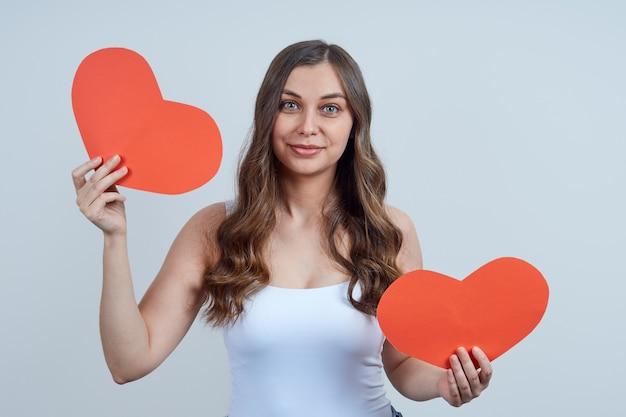 Een schattige jonge vrouw in een wit t-shirt, met twee rode harten in haar handen.