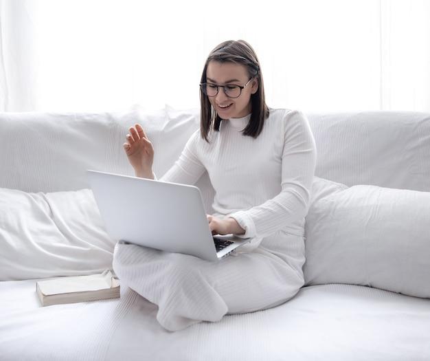 Een schattige jonge vrouw zit thuis op een witte bank in een witte jurk en werkt op een laptop.