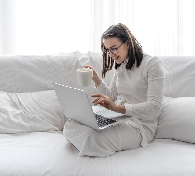 Een schattige jonge vrouw zit thuis op een witte bank in een witte jurk voor een laptop
