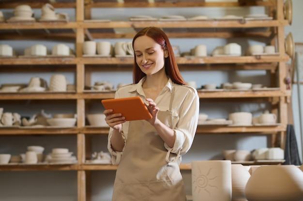 Een schattige jonge vrouwelijke pottenbakker met een tablet in handen