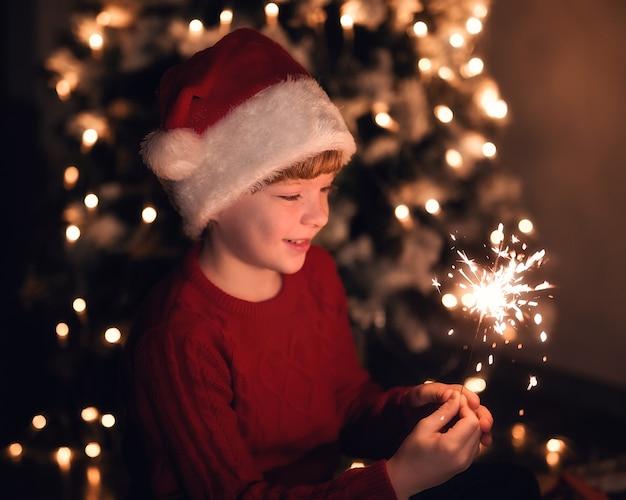 Een schattige jongen met een kerstmuts houdt brandende sterretjes vast tegen een achtergrond van gele lichten en een naaldboom.