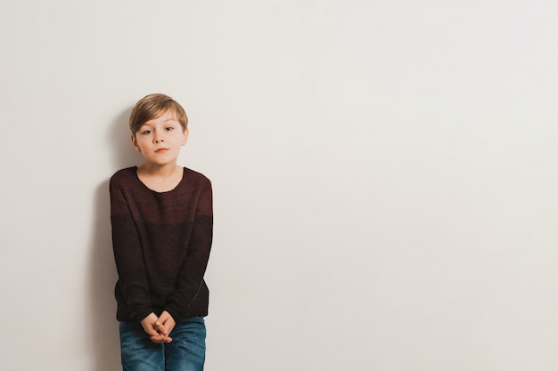 Een schattige jongen met een ongelukkig gezicht, leunt tegen een witte muur