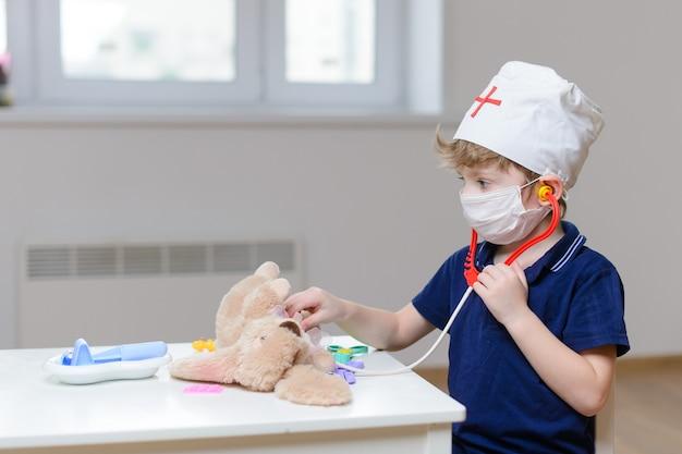 Een schattige jongen van 5 jaar speelt een dokter en zet een konijnenspeelgoed op met een statoscoop. de jongen zette een medisch masker op en een witte muts met een rood kruis.