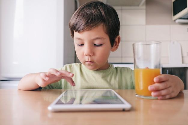 Een schattige jongen zit aan tafel, gebruikt een tablet en drinkt sap.