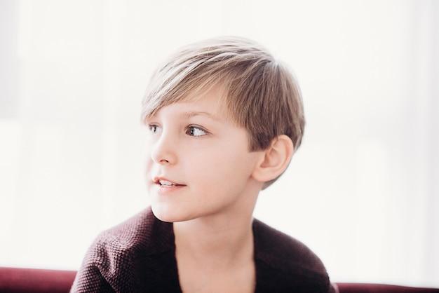 Een schattige jongen zit tegen het raam, zachte focus