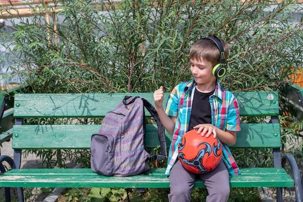 Een schattige jongensschooljongen gekleed in vrijetijdskleding luistert naar muziek met een koptelefoon, zit op een bankje, houdt een voetbal in zijn handen, een schooltas ligt in de buurt. terug naar schoolconcept