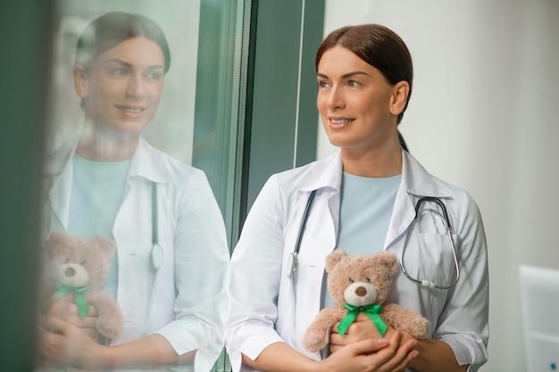 Een schattige kinderarts die bij het raam staat en een teddybeer vasthoudt