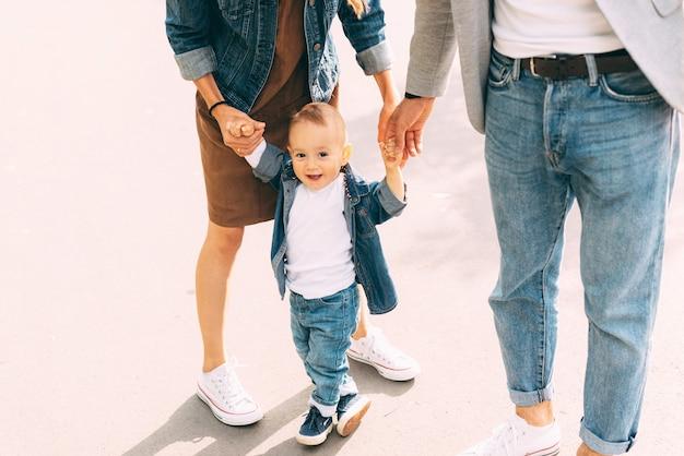 Een schattige kleine baby leert hoe hij dichtbij zijn ouders moet lopen