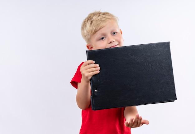 Een schattige kleine blonde jongen draagt een rode t-shirt met lege map op een witte muur