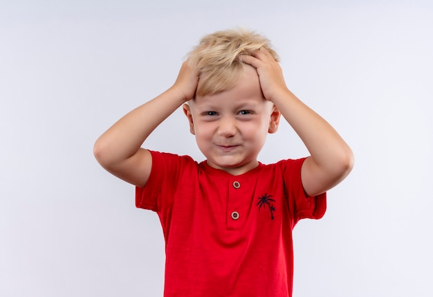 Een schattige kleine blonde jongen in het rode haar van de t-shirtholding met vingers