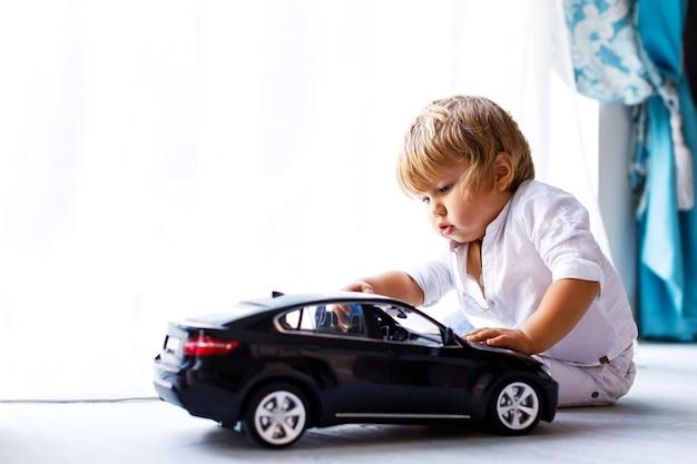 Een schattige kleine jongen die op de vloer van het huis zit en met een speelgoedauto speelt