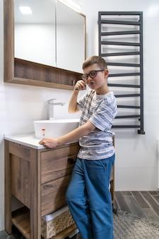 Een schattige kleine jongen die zijn tanden poetst en het uur bepaalt met een zandloper.