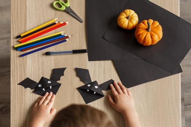 Een schattige kleine jongen maakte een halloween-vleermuis van zwart papier. handwerk voor kinderen.