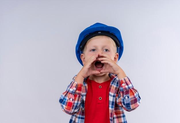 Een schattige kleine jongen met blond haar draagt een geruit overhemd in een blauwe helm die iemand belt met de handen op de mond op een witte muur