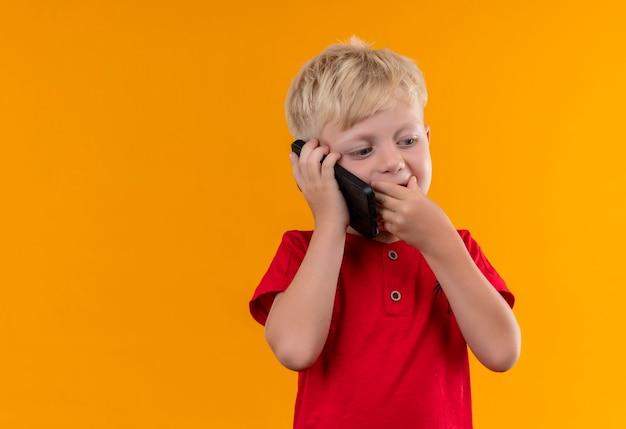 Een schattige kleine jongen met blond haar en blauwe ogen, gekleed in een rode t-shirt die op de mobiele telefoon spreekt