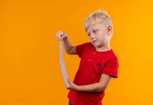 Een schattige kleine jongen met blond haar en blauwe ogen, gekleed in een rode t-shirt kijken naar notebook