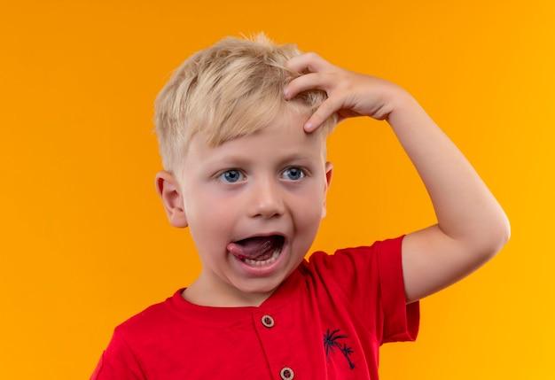 Een schattige kleine jongen met blond haar en blauwe ogen, gekleed in een rode t-shirt met hand op het hoofd met open mond