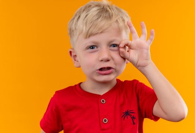 Een schattige kleine jongen met blond haar en blauwe ogen, gekleed in een rode t-shirt met ok gebaar met de hand
