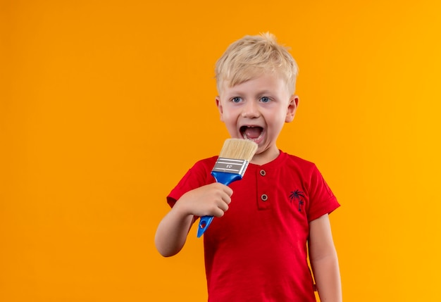 Een schattige kleine jongen met blond haar en blauwe ogen, gekleed in een rood t-shirt met een blauwe verfborstel dicht bij de mond en kijkt naar de zijkant op een gele muur