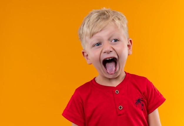 Een schattige kleine jongen met blond haar en blauwe ogen, gekleed in een rood t-shirt met zijn tong terwijl hij naar de zijkant kijkt