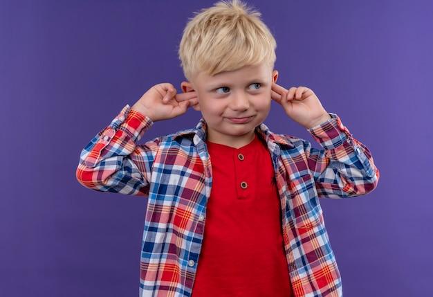 Een schattige kleine jongen met blond haar in een geruit overhemd met vingers op zijn oren op een paarse muur