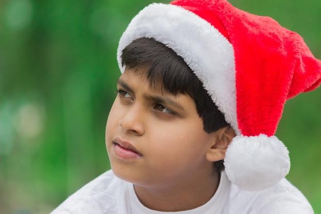 Een schattige kleine jongen met een kerstmuts die opzij kijkt in de verte