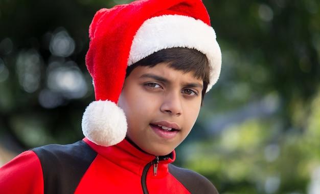 Een schattige kleine jongen met een rood t-shirt met kerstmuts, vrolijk glimlachend en kijkend naar de camera