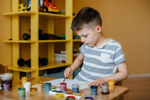 Een schattige kleine jongen speelt en schildert in zijn kamer. recreatie en amusement. blijf thuis.