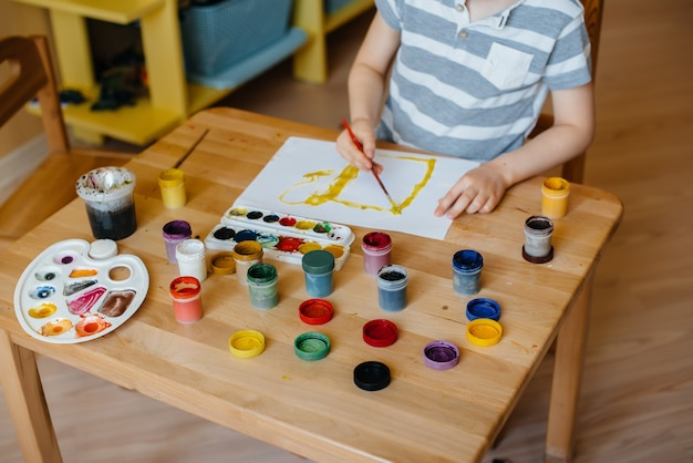 Een schattige kleine jongen speelt en schildert in zijn kamer. recreatie en vermaak. blijf thuis.
