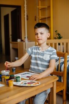 Een schattige kleine jongen speelt en schildert in zijn kamer