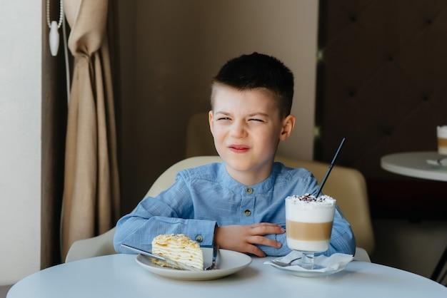 Een schattige kleine jongen zit in een café en kijkt naar een close-up van cake en cacao. dieet en goede voeding.