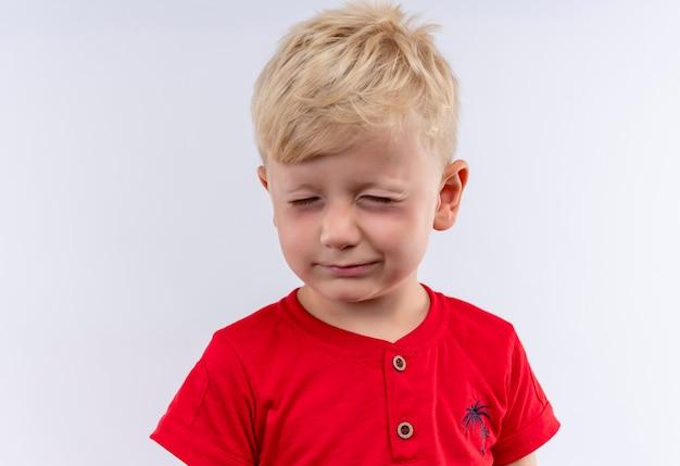 Een schattige kleine schattige jongen met blond haar, gekleed in een rood t-shirt dat zijn ogen sluit