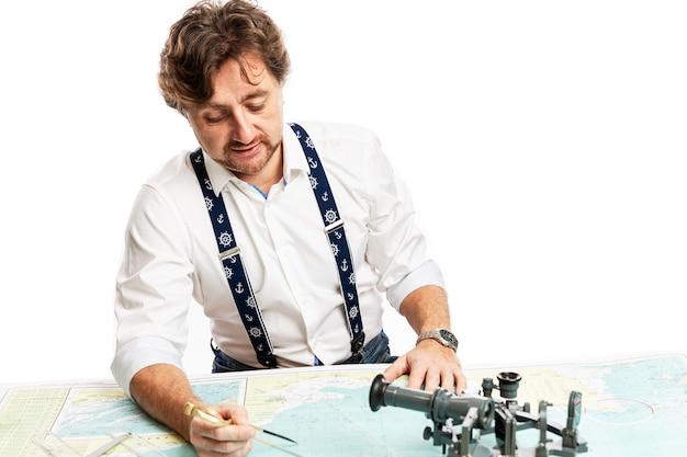 Een schattige lachende kapitein meet de afstand op een kaart met een kompas. geïsoleerd op een witte muur.