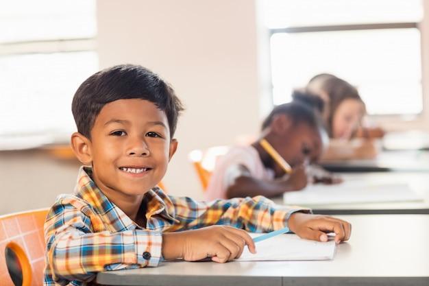 Een schattige leerling die zich voordeed aan zijn bureau