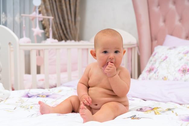 Een schattige, mollige naakte baby die naar de camera kijkt in een roze kinderkamer met wieg.