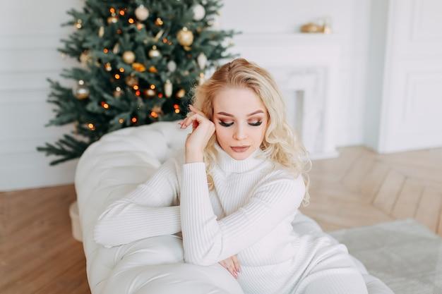 Een schattige mooie gelukkige jonge vrouw in een jurk rust zittend op een witte bank in de buurt van een kerstboom