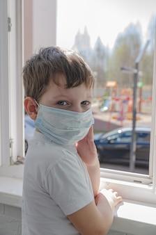 Een schattige trieste jongen van vier in een medisch masker zit op het balkon en kijkt uit het raam naar de speeltuin. zelfisolatie (quarantaine) als gevolg van de pandemie (epidemie) van het coronovirus