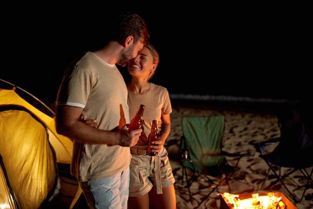 Een schattige vrouw en een knappe man brengen romantisch tijd door in de buurt van de tent bij het vuur en drinken bier op het strand aan zee.