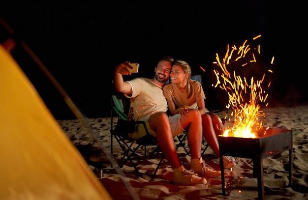 Een schattige vrouw en een knappe man brengen romantisch tijd door in de buurt van de tent bij het vuur, nemen 's nachts een selfie op een smartphone op het strand aan zee.