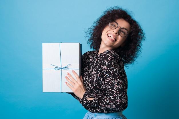 Een schattige vrouw met krullend haar en een bril toont haar tong terwijl ze een cadeautje vasthoudt op een blauwe muur